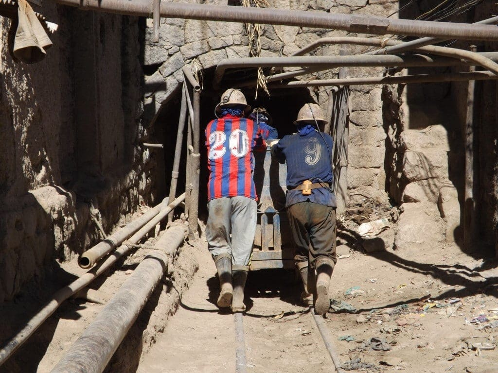 Miners pushing wagons by hand into the mine.
