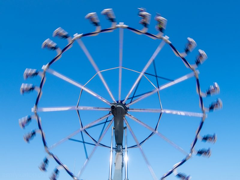 Spinning ride against blue sky