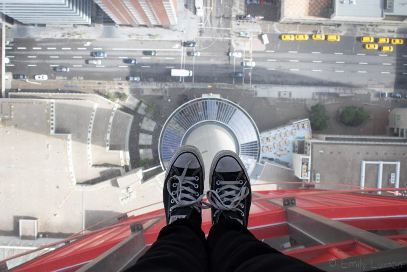 Converse shoes on a glass floor above a city street