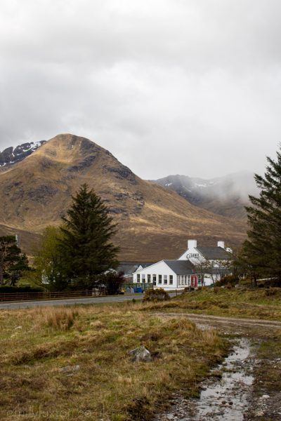Black Sheep Hotels Cluanie Inn tucked between pine trees beneath a mountain