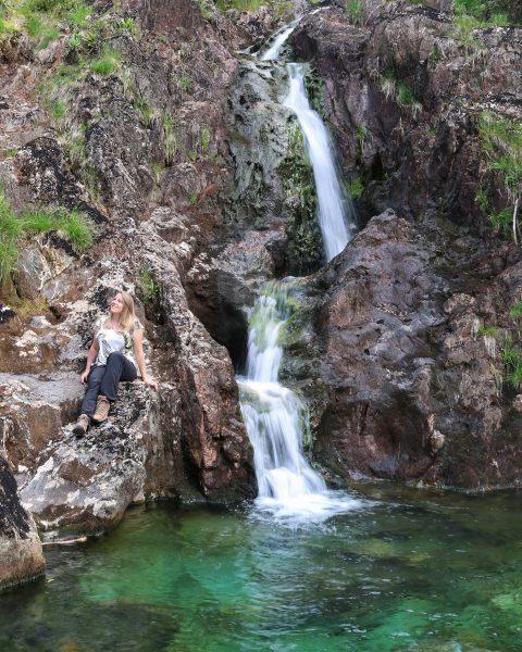 Emily sitting next to a waterfall near Dinas Emrys Snowdonia Wales