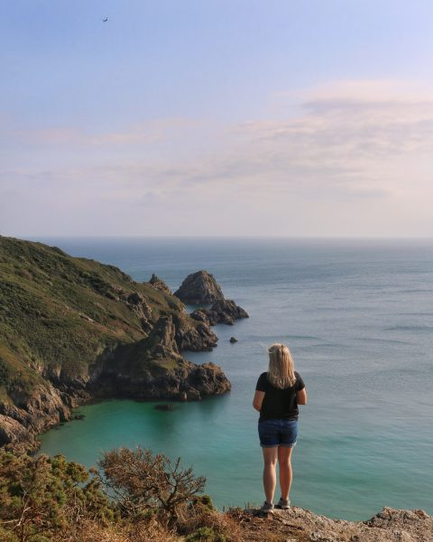 girl standing on a cliff at Petit Port in Guernsey - travel tips