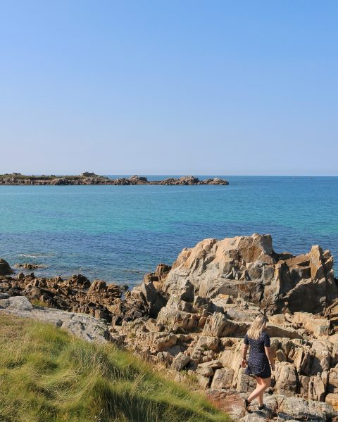 girl walking towards some rocks with the sea in the background