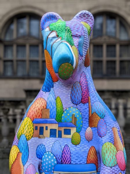 Bear painted purple with multicoloured trees and houses on it - part of the Sheffield Bears public art trail