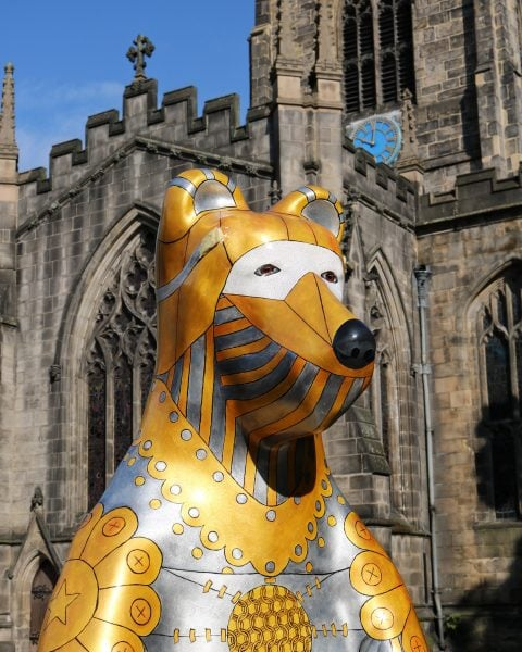 Gold and silver statue of a bear in front a cathedral - part of the heffield Bears public art trail